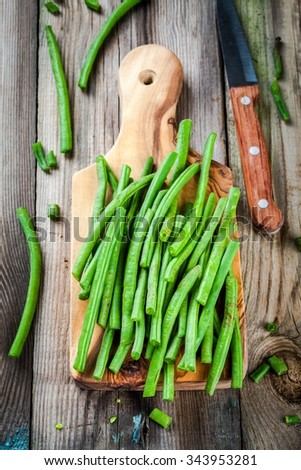 pods of fresh organic green beans in a wooden cuttin board on a rustic table - stock photo