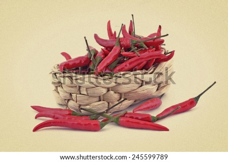 pods of red pepper in a wicker basket. Picture in retro style. - stock photo
