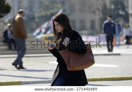 Poeple checking mobile phone on street in Istanbul, Turkey, 15 October, 2015 - stock photo