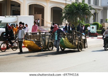 POI PET, THAILAND - JANUARY 19: People pull carts on the road on the Thai Cambodian border on January 19, 2011 in Thailand. - stock photo