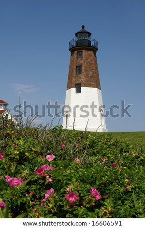 Point Judith Lighthouse, Rhode Island Vertical With Rugosa Rose Foreground and Copy Space - stock photo