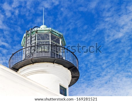 Point Loma lighthouse tower lantern detail.Circular shape white structure.Fresnel lens partly visible in window glass.Metal railing on balcony.Vent ball on top.Cloudy blue sky background. - stock photo