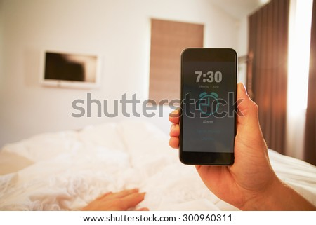 Point Of View Image Of Person In Bed Turning Off Phone Alarm - stock photo
