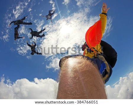 Point of view of a camera attached in the leg of the skydiver. Fish eye lens used, with the sun background. - stock photo