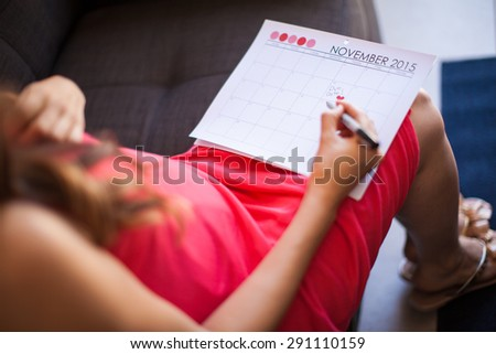Point of view of a young expentant mother marking the baby's due date on a calendar - stock photo
