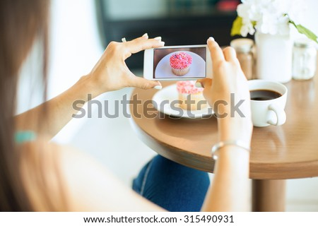 Point of view of a young woman taking a photo of her food with her smartphone. Picture of food on screen. - stock photo