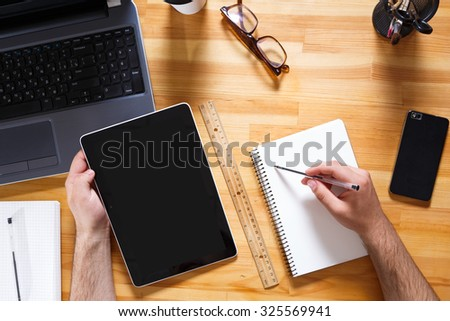 Point of view of businessman, sitting at the table and working with notebook and tablet. Glasses, coffee, smart phone and laptop are standing on the table, in the office, waist up - stock photo