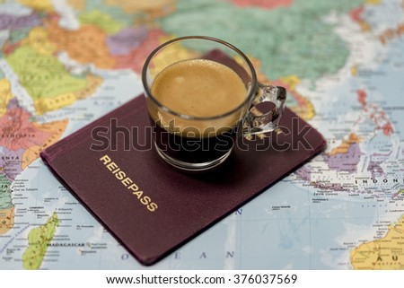 Point of view perspective of German passport on top of paper color map with glass of hot beverage - stock photo
