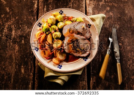 Point of view perspective of single plate filled with sliced stuffed pork roast, potatoes and brussels sprouts over wooden table - stock photo