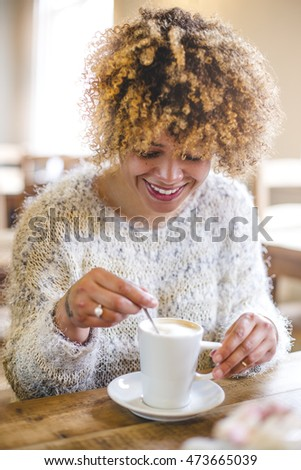 Point of view shot of a woman mixing her coffee in a cafe. She is laughing and looking down.