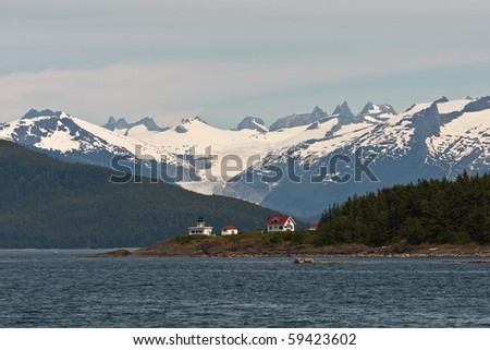 Point Retreat Lighthouse sits below a glacier in Juneau, Alaska. - stock photo