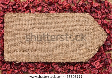 Pointer of burlap lying on a dry cranberry background, with place for your text - stock photo