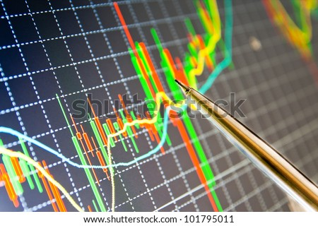 Pointing a pen at the chart, analyzing stock chart on a computer screen