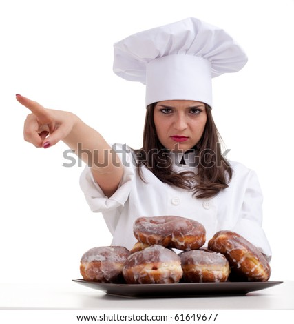 pointing angry female chef in white uniform and hat with doughnuts