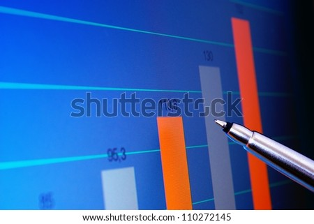Pointing at financial analysis graph on computer monitor with pen - stock photo