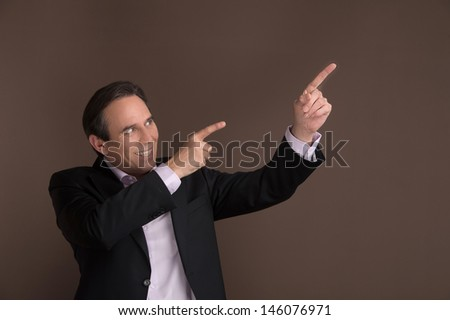Pointing away with enthusiasm. Cheerful mature businessman pointing away while standing on brown background - stock photo