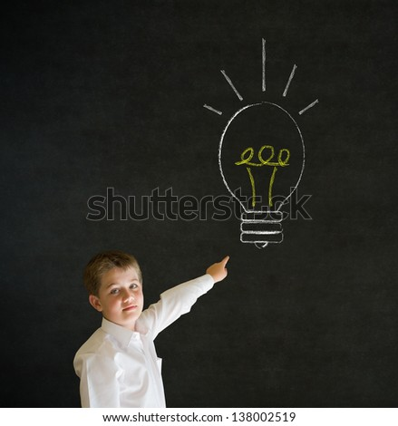 Pointing boy dressed up as business man with bright idea chalk background lightbulb on blackboard background - stock photo