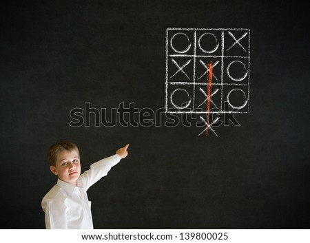 Pointing boy dressed up as business man with thinking out of the box tic tac toe concept on blackboard background - stock photo