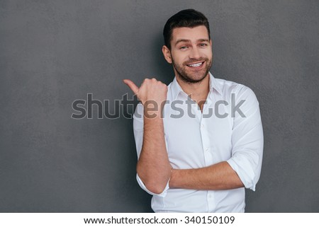 Pointing copy space. Handsome young man pointing copy space and smiling while standing against grey background  - stock photo