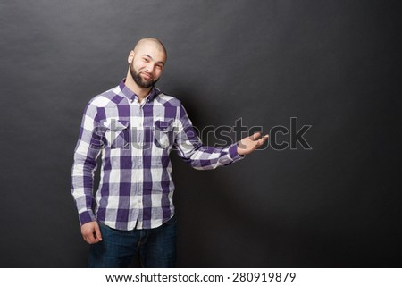 Pointing copy space. Happy young bearded man in casual wear looking at camera and smiling while standing against black background and pointing away. - stock photo