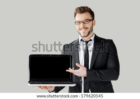 Pointing copy space on his laptop. Handsome young man in formalwear and glasses holding a laptop and pointing it while standing against grey background - stock photo