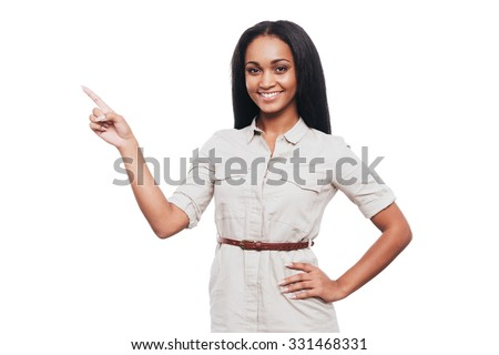 Pointing copy space. Smiling young African woman holding hand on hip and pointing away while standing against white background - stock photo