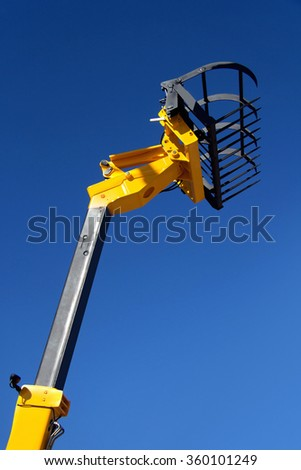 Pointing forklift, loader against the blue sky, seizure of hay, unloading cargo, agricultural machinery, hydraulic capture truck, farm equipment, heavy forklift yellow. - stock photo