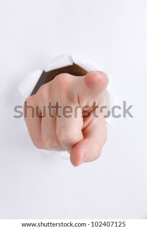 Pointing hand breaking through the paper