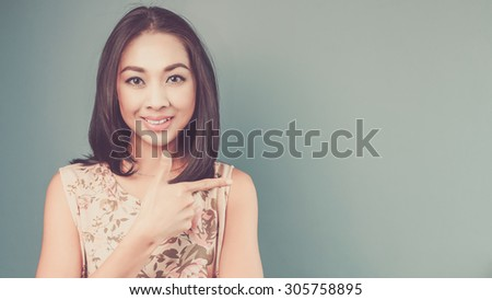 Pointing on copyspace. Vintage, retro style of portrait of Asian woman in pink vintage dress on blue and green background. - stock photo