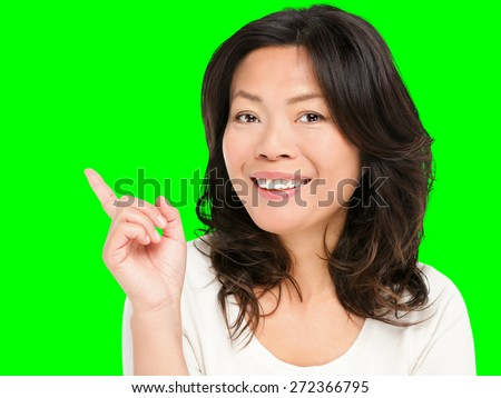 Pointing showing Asian woman. Middle aged Chinese Asian woman pointing and showing smiling happy. Female model in her early 50s isolated cutout on green chroma key background. - stock photo