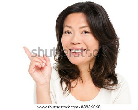 Pointing showing Asian woman. Middle aged Chinese Asian woman pointing and showing smiling happy. Female model in her early 50s isolated on white background. - stock photo