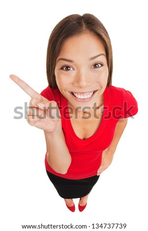 Pointing showing woman. Humorous high angle studio portrait of a grinning woman pointing to the left of the frame with her finger. Mixed race Asian Caucasian business woman isolated white background - stock photo