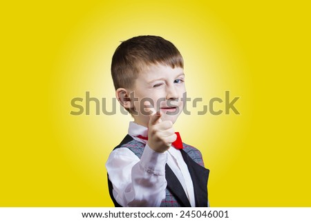 Pointing to camera funny little boy with one eye closed isolated over yellow background. - stock photo