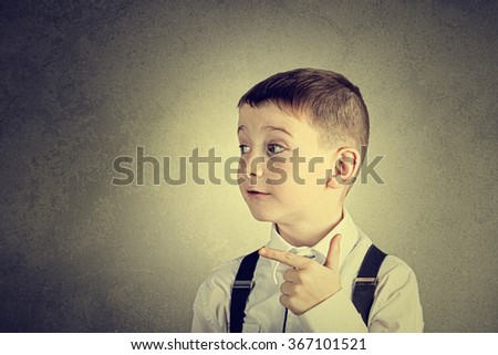 Pointing to right little boy isolated over yellow background. - stock photo