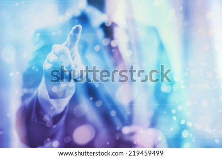 Pointing towards camera and pressing virtual screen button, copy space for charts and ui. - stock photo