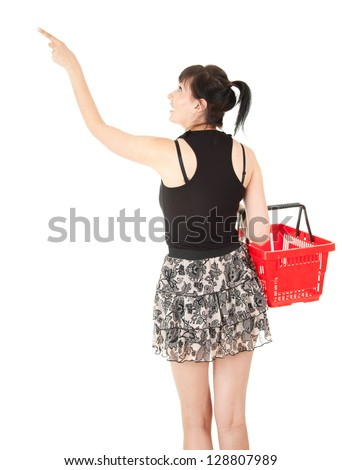 pointing up lyoung woman with red shopping basket, white background - stock photo