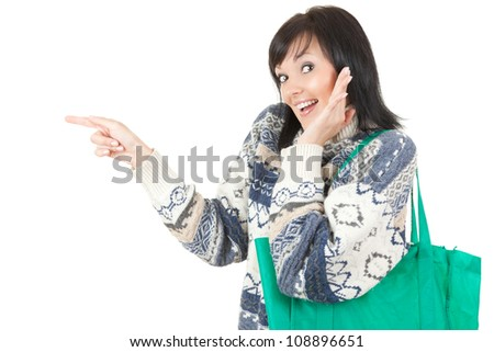 pointing young surprised woman with green ecological shopping bag, white background