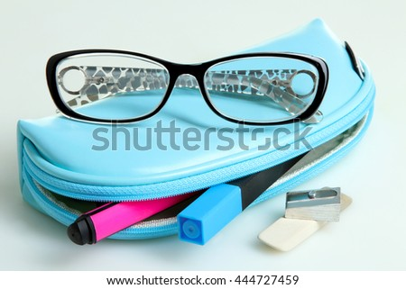 points on the pencil case with markers and pencil sharpener with eraser on white isolated background - stock photo
