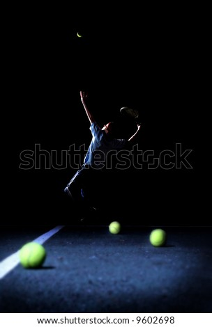 Poise and Focus- A Teenager Practicing His Tennis Serve - stock photo