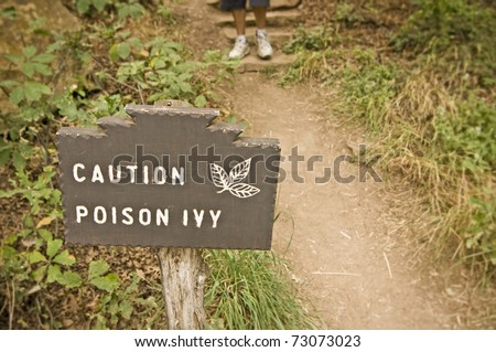 Poison Ivy (Toxicodendron radicans) sign with hiker in background. - stock photo
