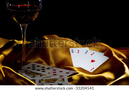 "poker ace and a glass of wine on a golden silk. low key shot with focus on the 4 ""A"" - stock photo"