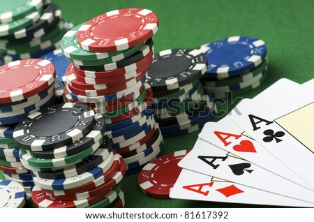 poker aces and gambling chips  stacked on a table - stock photo