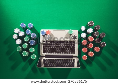 Poker and casino online gaming concept with laptop and stacks of chips on green table, top view - stock photo