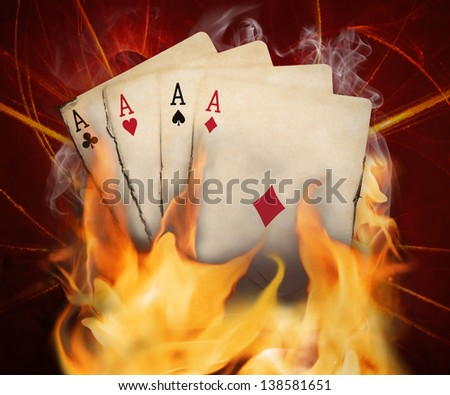 Poker cards burn in the fire. - stock photo