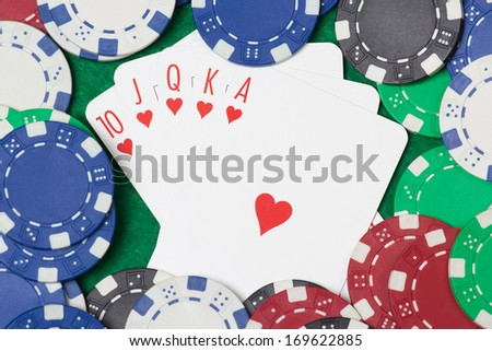 Poker cards with royal flush combination and chips on green casino table