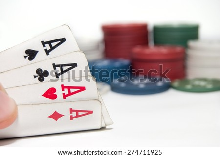 Poker chips and a hand hold the cards isolated