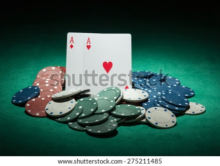 Poker chips and ace cards on green background - stock photo