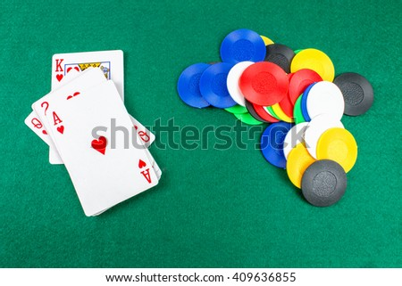 Poker Chips and Cards on Gambling Green Table.