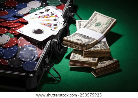 Poker chips and dollar bills onon black background - stock photo
