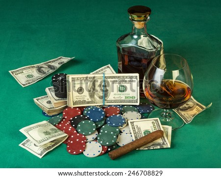 Poker chips and dollar bills with cognac on green cloth - stock photo